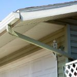 Gutters hang off the edge of a roof with a downspout going off of it and a view of soffit and fascia