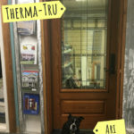 Boston terrier posing next to an entry way door display in ABC office