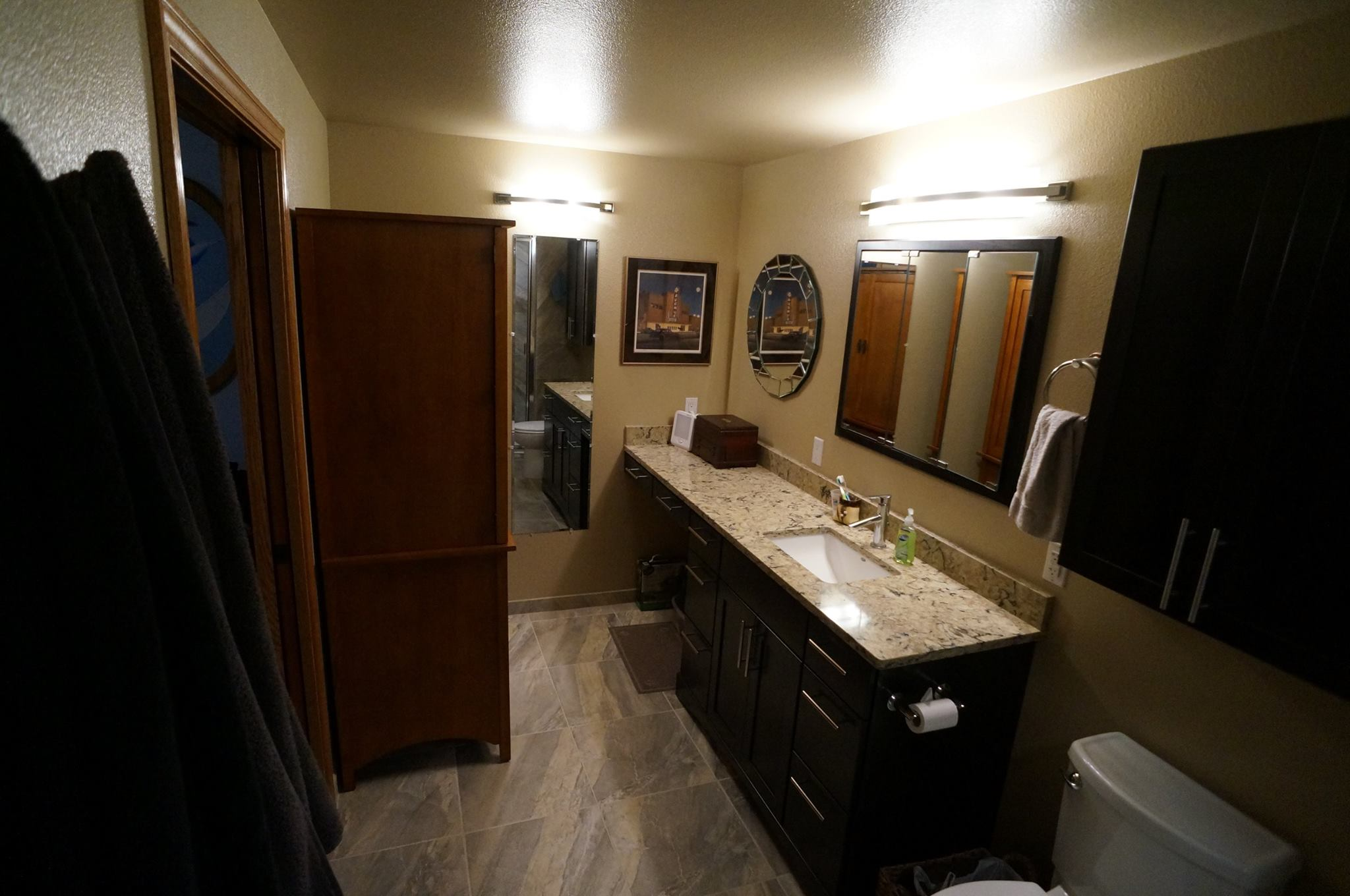 Remodeled bathroom with dark cabinets and granite counter tops on vanity