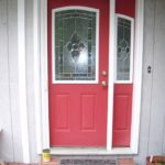 Front porch with bright red door and white frame