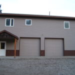 Newly remodeled house with tan siding and two garage doors