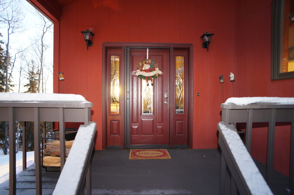 Snowy front porch with dark red door
