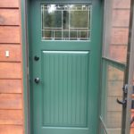 Green door with glass window and screen door