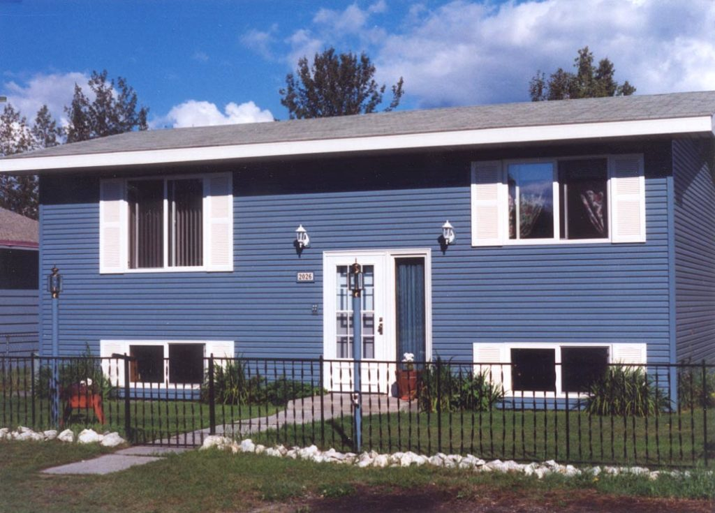Newly completed house with blue steel siding, white doors and windows