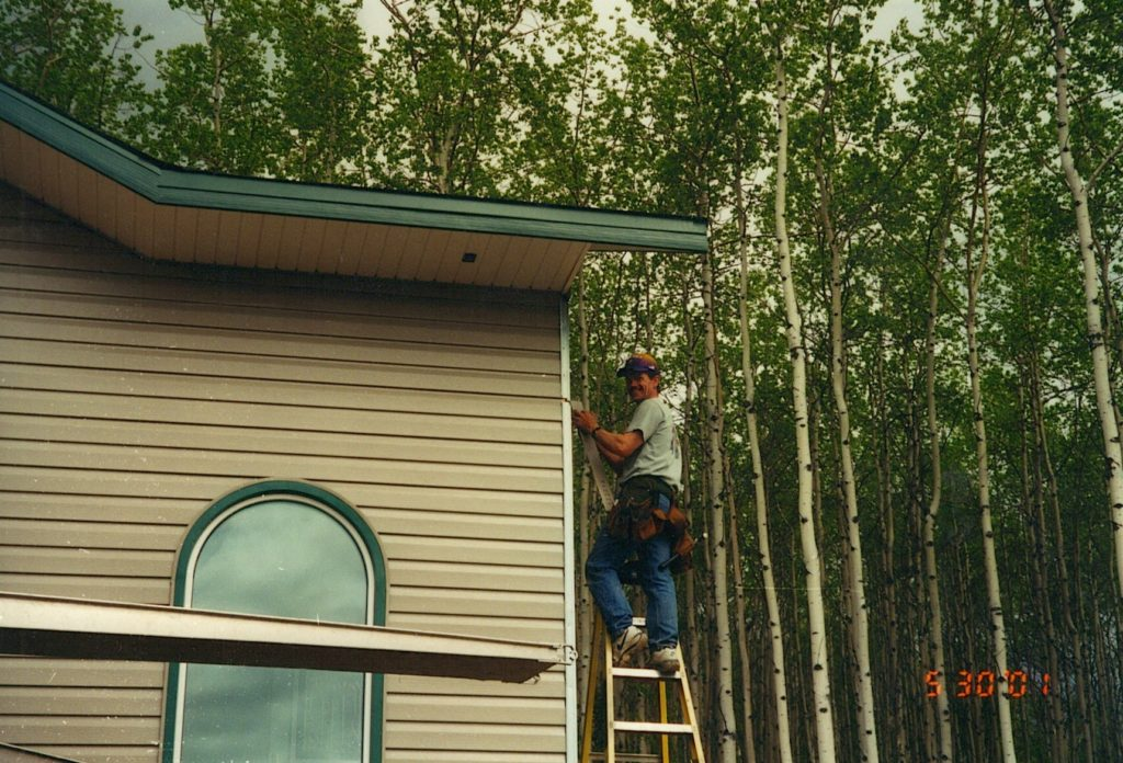 Man posing on ladder while putting up steel siding on house
