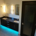 Bathroom with interesting blue recessed lighting underneath cabinets