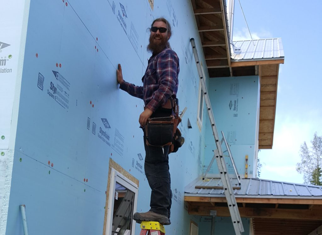 Man posing on a ladder while putting up siding on house