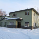 Snow-covered house with green steel siding