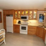 Kitchen featuring stain-glass paneled tan cabinets