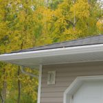 Gutters, soffit, and downspouts on the corner of a house in fall
