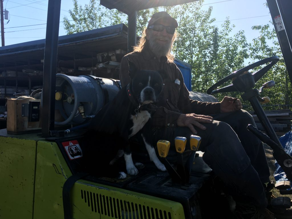 Employee of ABC Inc riding a fork lift with boston terrier